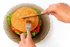 Hamburguesa grande en un rato de la comida de placa Foto de archivo libre de regalías
