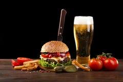 Hamburguesa hecha en casa con las patatas fritas y la botella de cerveza que vierten en un vidrio Comida rápida en fondo oscuro e imagen de archivo