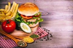 Hamburguesa hecha en casa deliciosa con la ensalada y las especias frescas Fotografía de archivo libre de regalías