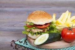 Hamburguesa hecha en casa deliciosa con las fritadas, lechuga, tomate del pollo Imagenes de archivo