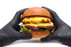 Hamburguesa jugosa de la hamburguesa con queso, la cebolla, las patatas y la ensalada en un fondo blanco en manos con los guantes fotografía de archivo