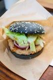 Hamburguesa negra con el cerdo y la salsa picante envueltos con el papel Imagen de archivo libre de regalías