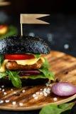 Hamburguesa negra con la chuleta, verdes, queso, cebollas y tomates en una placa de madera en una tabla oscura fotos de archivo