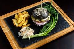Hamburguesa negra con las cebollas y los pepinos en la tabla de piedra con el fondo negro Fotografía de archivo libre de regalías