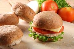 Hamburguesa, panes y frutas imagenes de archivo