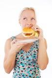 Hamburguesa rubia atractiva de la consumición Foto de archivo libre de regalías