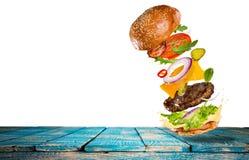 Hamburguesa sabrosa grande con los ingredientes del vuelo ilustración del vector