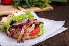 Hamburguesa tirada del cerdo con el tomate de la ensalada de col, la cebolla y el pan fresco Foto de archivo