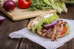 Hamburguesa tirada del cerdo con el tomate de la ensalada de col, la cebolla y el pan fresco Imágenes de archivo libres de regalías