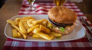 Hamburguesa y fritadas en una placa Fotografía de archivo