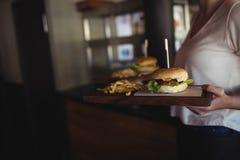 Hamburguesa y patatas fritas que llevan de la mujer en una bandeja en el restaurante Fotografía de archivo