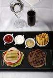 Hamburguesa y patatas fritas servidas en manera clásica Foto de archivo
