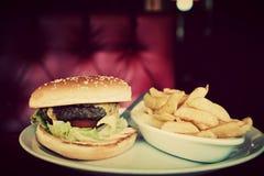 Hamburguesa y placa de las patatas fritas en restaurante americano de la comida Imagen de archivo libre de regalías