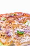 Hamburguesa y salchichas asadas a la parrilla del pollo con las verduras Imagen de archivo libre de regalías