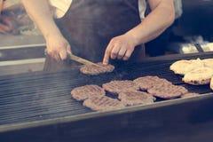 Hamburguesas asadas a la parrilla en parrilla del Bbq del carbón de leña Foto de archivo