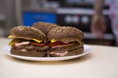 Hamburguesas clásicas con tocino, carne, queso, cebollas, tomates y queso y un bollo entero En la placa Primer imagen de archivo libre de regalías