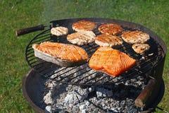 Hamburguesas del pollo o del pavo y pescados de color salmón en parrilla Fotografía de archivo