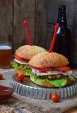 Hamburguesas del Veggie con la tajada de la berenjena, lechuga, cebollas conservadas en vinagre, tomate en un fondo de madera mar Fotografía de archivo libre de regalías