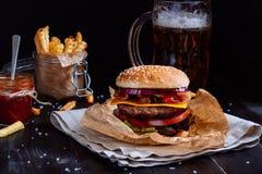Hamburguesas deliciosas frescas con las patatas fritas, la salsa y la cerveza en la tabla de madera Imagenes de archivo