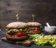 Hamburguesas hechas en casa apetitosas con el pollo en salsa de mostaza con arugula e hierbas en un área de texto de la tabla de  Imágenes de archivo libres de regalías