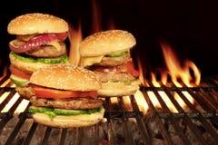 Hamburguesas hechas en casa de los cheeseburgers en la parrilla llameante caliente del Bbq Imagen de archivo