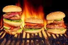 Hamburguesas hechas en casa de los cheeseburgers en la parrilla llameante caliente del Bbq Fotos de archivo libres de regalías