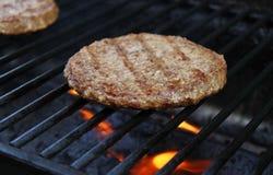 Hamburguesas que cocinan sobre las llamas en la parrilla Foto de archivo libre de regalías