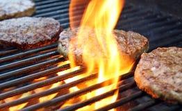 Hamburguesas que cocinan sobre las llamas en la parrilla Imágenes de archivo libres de regalías