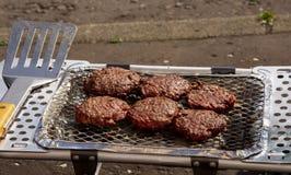 Hamburguesas que son cocinadas en el Bbq portátil Imagen de archivo