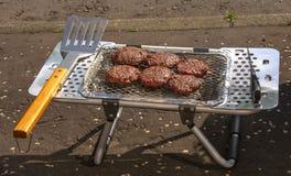 Hamburguesas que son cocinadas en el Bbq portátil Imagenes de archivo
