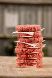 Hamburguesas sin procesar para las hamburguesas, en una pila Foto de archivo
