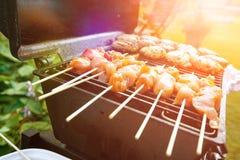 Hamburguesas y kebabs del pollo en la barbacoa caliente al aire libre en el sol de la tarde Imágenes de archivo libres de regalías