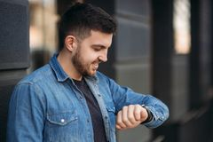 Hamdsome beard man taking a call on his watch royalty free stock images