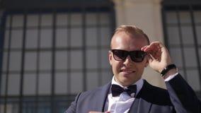 Hamdsome och stilfull brudgumställning på trappa Han bär solglasögon Mode Full HD-video stock video