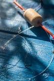 Hameçon sur la ligne de pêche et flotteur sur un fond bleu Image libre de droits
