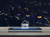 Hamer en moersleutel met huispictogram op het moderne slimme telefoonscherm o Stock Afbeeldingen