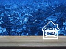 Hamer en moersleutel met huispictogram over antenne van modern stadsslepen Stock Fotografie