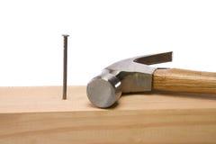 Hamer en spijker die op houten baksteen op wit wordt geïsoleerdk royalty-vrije stock foto's