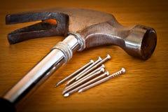 Hamer en spijkers op een houten achtergrond Stock Foto's