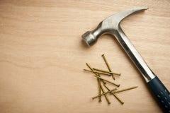 Hamer en spijkers op houten plank stock afbeelding