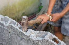 Hamer in hand brekende bakstenen muur Stock Afbeelding