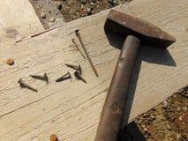 Hamer met spijkers die op houten plank leggen Stock Fotografie