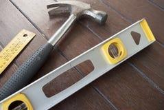 Hamer, niveau en de vierkante heerser van t op houtachtergrond Royalty-vrije Stock Afbeeldingen