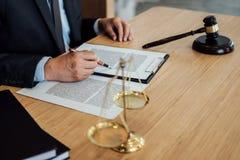 Hamer op houten lijst en Advocaat of Rechter die met overeenkomst in Rechtszaalthema, Rechtvaardigheid en Wetsconcept werken stock foto's
