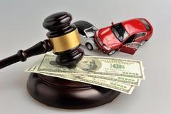 Hamer van rechter met geld en stuk speelgoed auto's op grijs Stock Foto