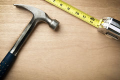 Hamer y cinta de medición en el fondo de madera Foto de archivo