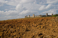 Hamlet of Monteriggioni. Ploughed clay farmlands around the hill top hamlet of Monteriggioni, Tuscany, Itlaly Stock Image