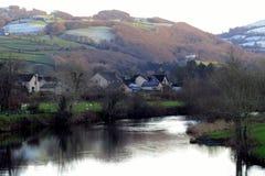 Hamlet, riverside, beneath green and frosty hillside Stock Photo