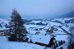 Hamlet in snowy mountains. Scenic aerial view of hamlet or village in snowy mountains at dusk, winter scene Stock Images
