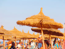 Tourists on Tunisian beach. Tourists under thatched beach umbrellas in Tunisia stock image